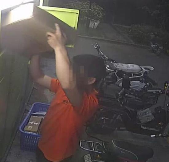 快递员起初将包裹放进快递箱
