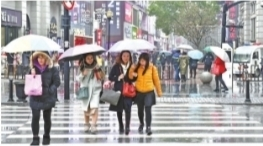 江汉路步行街上的行人撑起伞走在冷雨中 记者李永刚 摄