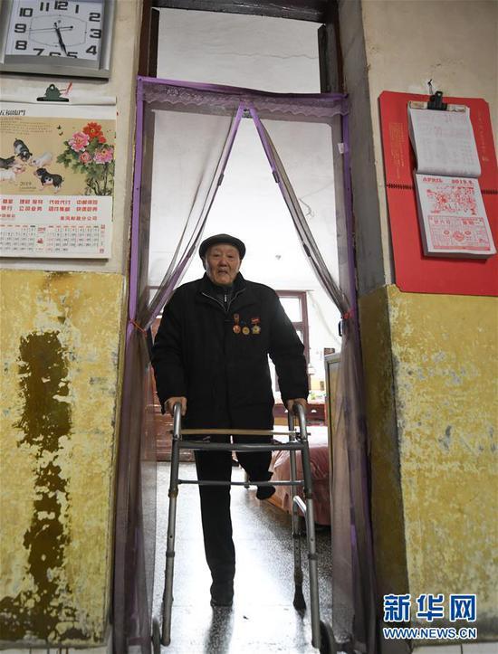 左腿截肢的张富清依靠支撑架在家里活动(3月31日摄)。新华社记者 程敏 摄