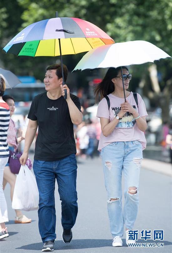 5月16日,游人在杭州西湖断桥上游览。近日,浙江杭州最高温度持续35摄氏度以上。据浙江省气象台分析,5月15日至17日三天受副高边缘影响,浙江将持续高温,全省除沿海地区外大部最高气温达35摄氏度至37摄氏度。新华社记者翁忻旸摄