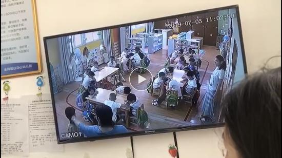 幼儿园老师拉扯男童的耳朵。 视频截图