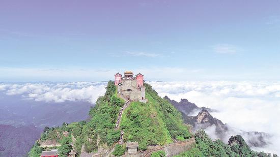 """""""惠游湖北""""活动启动以来,大量游客涌入武当山。图为游客们攀登武当金顶。 (通讯员 彭涛 摄)"""