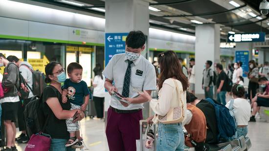 """武汉地铁""""姚婕志愿服务总队""""在武汉火车站发放《乘地铁 游武汉》手册"""