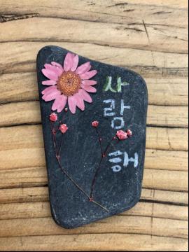 新浪湖北记者在老师的指点下,用乌石和干花制作了一个冰箱贴
