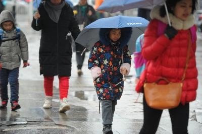 新一轮雨水又要来了。昨日,孩?#29992;?#22312;?#39029;?#38506;伴?#26053;白?#39118;雨上学记者肖僖 摄