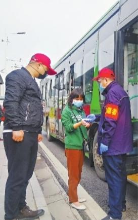 22日8时30分许,东西湖大道额头湾公交站,准备上车的乘客接受体温测量 长江日报记者张宁 摄