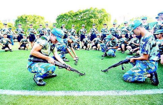 图为华中师范大学新生军训时练习拆装枪械