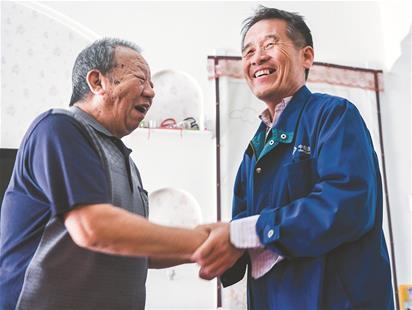 图为崔爱民(右)紧紧握住救命恩人向国洪的手