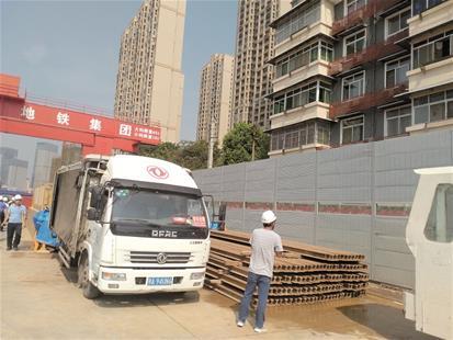 图为工地和居民楼之间新安装了隔音墙