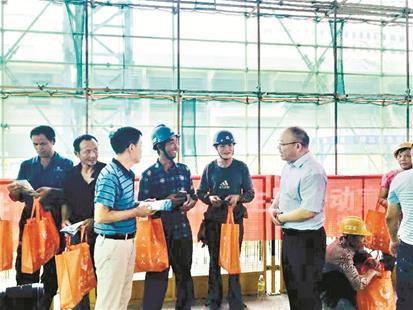 图为:洪山区司法局党组书记、局长刘光平(右一)深入工地,与农民工兄弟交谈