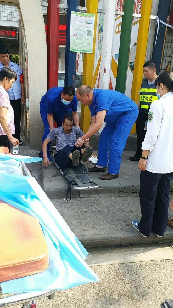 城管员协助医护人员帮老人上担架