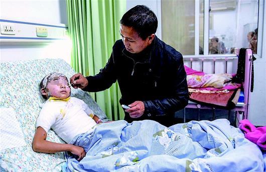 图为:父亲李太和用棉签给女儿涂抹药膏
