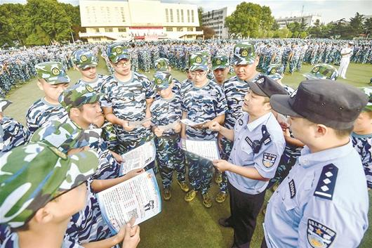 图为:洪山区南湖派出所民警在高校开展防骗宣传