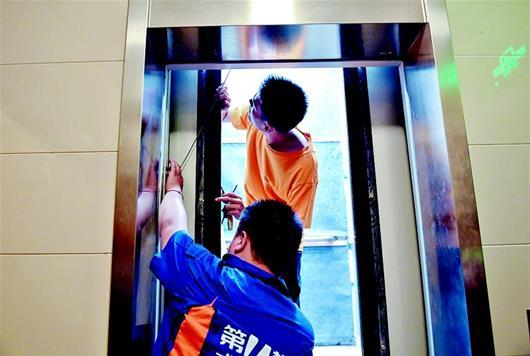图为维修人员在检查损坏的电梯
