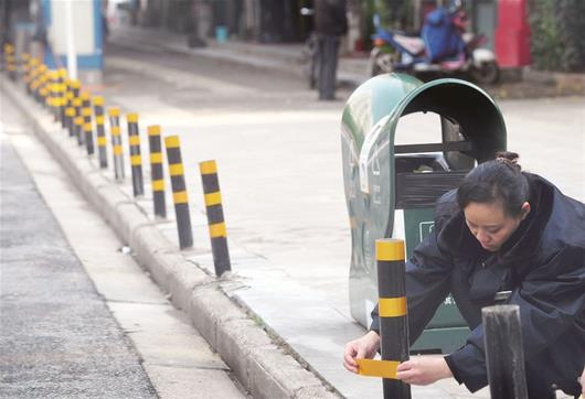 图为:一名物业工作人员正在路边设立路桩