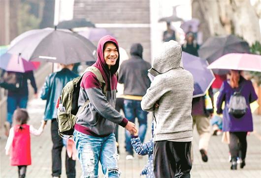 图为武汉昨日冷雨,年轻人已穿上厚衣
