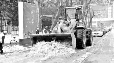 昨日,在汉口永清街,由市政工人和城管等部门组成的除雪大军正在清除街面的冰雪记者喻志勇 摄