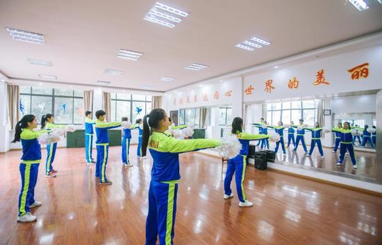 (图说:武汉市第二聋哑学校啦啦操队员在进行训练)