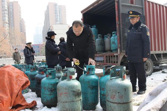 硚口区城管委主任严栓主任(右二)检测燃气坛子质量