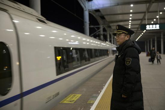 除夕夜21点37分,信阳东站客运值班员冯明立岗送车。今年是他在岗位上连续度过的第3个除夕之夜。刘鑫 摄