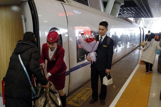 蔡鹏为不影响妻子工作,站在旁边看着妻子组织旅客乘降。姜小武 摄