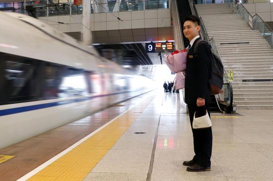 蔡鹏捧着鲜花在站台上看着妻子值乘的G492次列车驶入武汉站。姜小武 摄