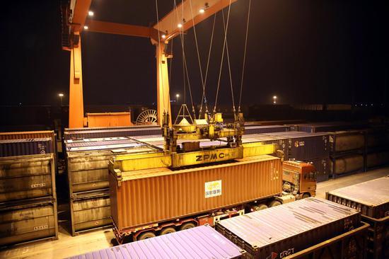 正面起重机正在进行(中欧班列)集装箱夜间调车作业(摄影:丁旭 熊文攀)