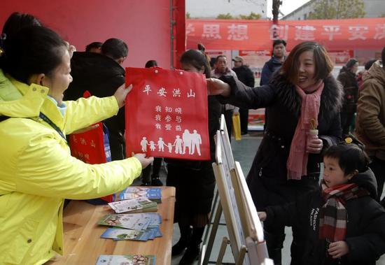 洪山社工向居民免费发放家庭防火手册、禁毒手册