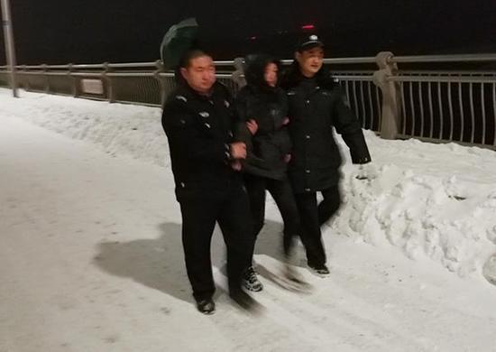 民警将女子带下桥。警方供图