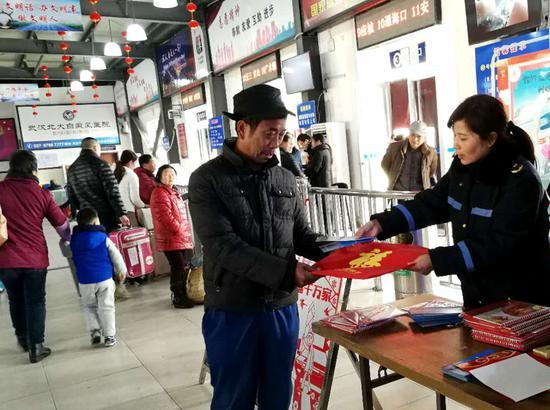 硚口城管委交通执法人员在古田客运站向旅客发放宣传卡及赠送年历福。