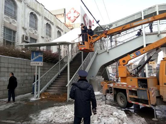 硚口城管执法人员对太平洋跨街人行天桥顶棚积雪和棚檐冰锥进行清理