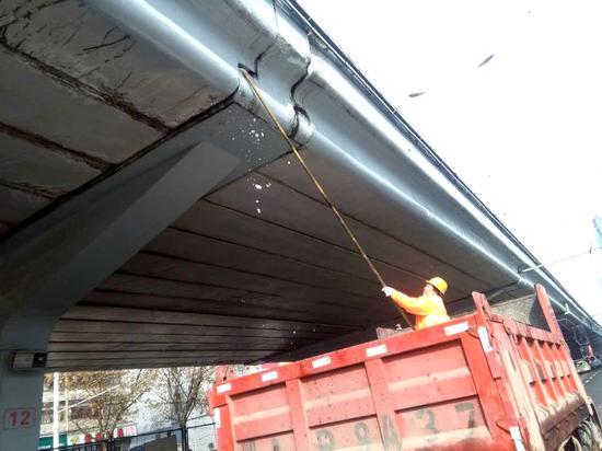 硚口城管委道桥队工人将武胜路高架桥桥檐下的冰锥敲落