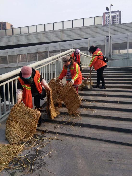 硚口区环卫工人清理利济北路人行天桥台阶上的防滑草垫