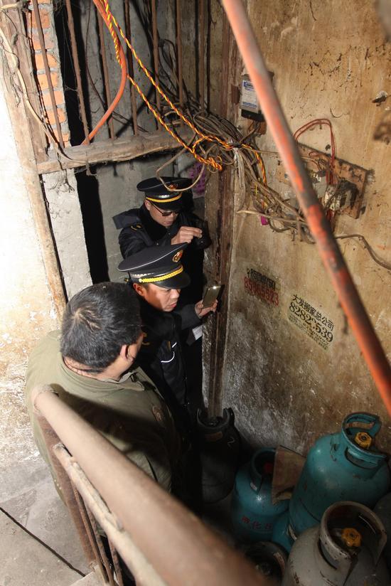 执法人员进入藏匿非法燃气坛子的窝点