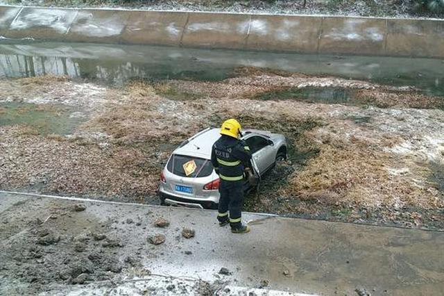 武汉一小车因雨雪天打滑冲至路边水渠 3人被困车内