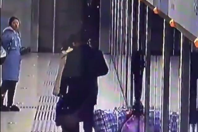危险!男子强行冲入地铁车厢 随身行李被卡住