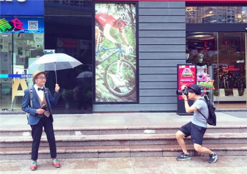 路边,丁炳才撑着伞,杰西端着相机,正在为爷爷拍摄时尚大片。