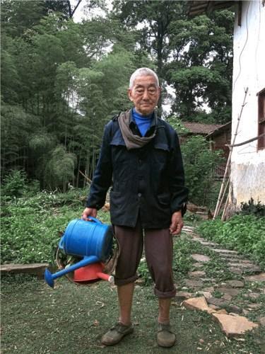 蓝灰色的厚布衣服,军绿色解放鞋,棕色的裤子经常挽到膝盖,这是85岁的丁炳才以往的样子。
