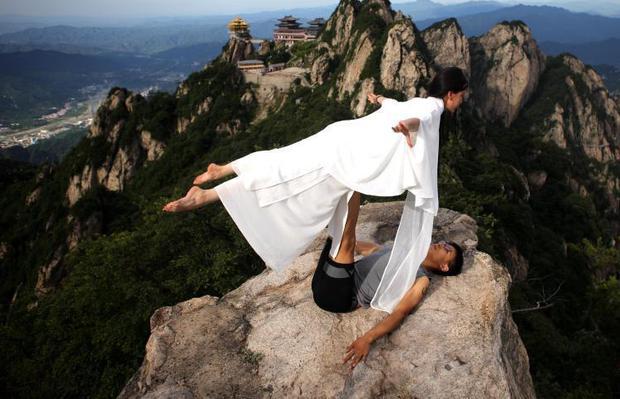 美女悬崖绝壁上练瑜伽