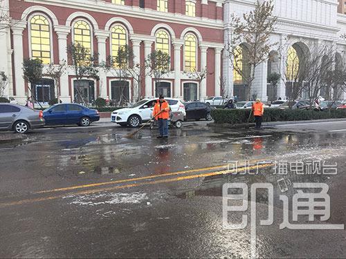 清洁人员正在清扫路面,他们告诉记者,十分钟清一次,还是有积水。刘潇 摄