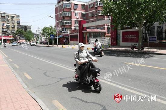 """14日,山东济南天气晴热,公众""""全副武装""""防晒。(图/王连珍)"""