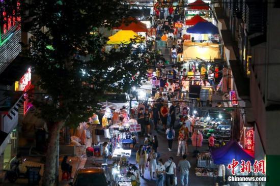 6月3日,市民在武汉保成路夜市消费休闲。随着复工复产复市持续推进,武汉传统的街头夜市热闹起来,不少市民前来消费休闲。中新社记者 张畅 摄
