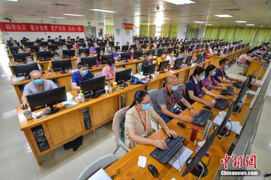 资料图:7月17日,评卷教师们佩戴口罩在位于海南师范大学的海南高考评卷现场工作。中新社记者 骆云飞 摄