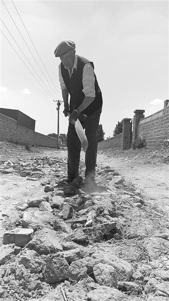 王忠义老人正在垫石修路。