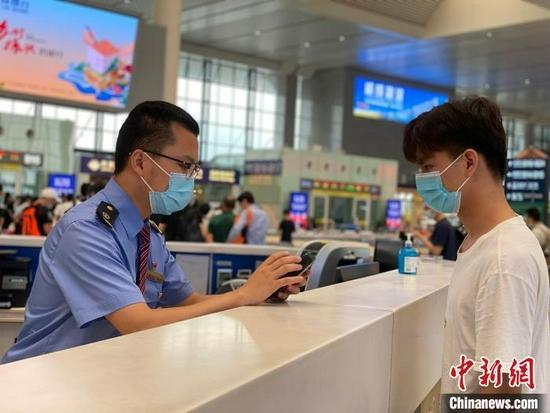 资料图:车站工作人员帮助旅客查询行程信息 于莉 摄