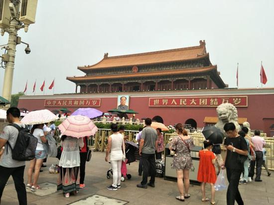 7月1日,北京天气闷热,游客打伞防晒。(来源:微博)