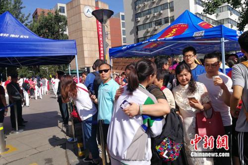 6月7日早上,一位家长在人大附中考场外与参加高考的孩子拥抱。