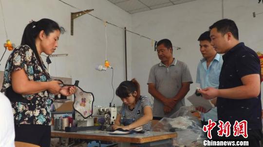 """""""脱贫小院""""里,工人们正在加工童车缝纫座套。 李铁锤 摄"""