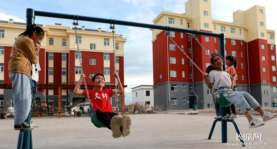 孩子们在张北县一个空心村治理易地新建安置点公会镇公会新区玩耍。