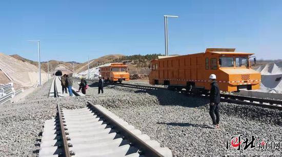 建设者在崇礼铁路下花园区段加紧补砟施工场景。